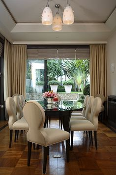 The round, glass-topped dining table and upholstered dining chairs are by Primafil, while the light fixture is from Arrakis Oggetti. The dining area has a lovely view of the garden, too, via sliding doors that open up for an al fresco vibe. A doorbell on the floor calls househelp during formal meals.