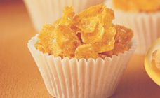 HONEY JOYS -90g butter or margarine -1/3 cup sugar -1 tablespoon honey -4 cups Corn Flakes Method: -Preheat oven to 150°C. -Line 24 hole patty pan with paper cases. -Melt butter, sugar and honey together in a saucepan until frothy. -Add Kellogg's Corn Flakes and mix well. -Working quickly spoon into paper patty cases. -Bake in a slow oven 150°C for 10 minutes. -Cool in fridge