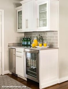 Contemporary kitchen bar features white cabinets fitted with a glass door beverage fridge and a stainless steel mini fridge paired with gray quartz countertops fitted with a farmhouse sink and a pull out faucet as well as gray subway tiled backsplash.