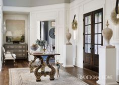 """Double doors open to the spacious foyer anchored by a """"Trieste"""" table from Formations. - Photo: Emily Jenkins Followill / Design: Amy Morris"""