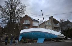 People examine the wreckage of a boat washed ashore in Great Kills, Staten Island, following Hurricane Sandy in New York, on October 31, 2012. The boat settled on Mansion Avenue after the storm surge from the hurricane saw waters rise 15 feet in the area.