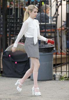 High heeling it: Emma strolled down the sidewalk in white platform heels...