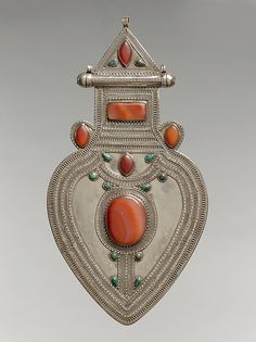 Pectoral Ornament 19th–20th century Geography: Central Asia or Iran Culture: Islamic Medium: Silver, with decorative wire, cabochon and slightly-domed carnelians, and turquoises Dimensions: 12 3/8 x 6 3/8 in. (31.4 x 16.2 cm)