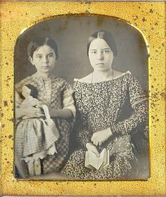 1/6 plate daguerreotype of two girls most likely sisters posed with a large doll and a book