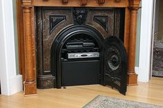 The components of the entertainment system are behind the old coal fireplace door.