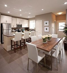 Stunning open plan kitchen and dining room with mocha walls and generous recessed lighting over custom white shaker cabinets and breakfast bar paired with dark brown countertops and ivory leather barstools.