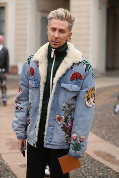 Street Style masculino em Milão com look todo escuro e jaqueta jeans com bordados