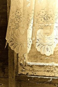 Love the softness of the sheer lace against the old chippy wooden & weathered wondow frame!