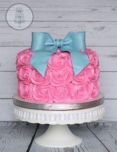 Pink and blue Gender reveal cake.  Pink rosettes and blue fondant bow