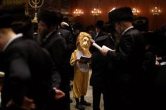 Abir Sultan—EPA: Feb. 24, 2013. Ultra-Orthodox Jewish men and a boy in a lion's costume read from the Scroll of Esther during the Purim festival at a synagogue in the neighborhood of Mea Shaarim in Jerusalem