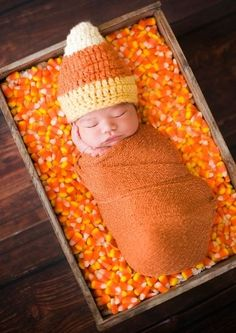 Baby laying in candy corn wearing a candy corn hat and swaddled in an orange blanket ~ Cute for harvest time photo