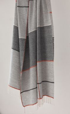 woven wool blanket in shades of gray with red, orange, blue, and white accents