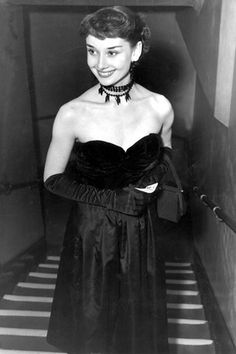 Audrey Hepburn 1955 - In a strapless gown and beaded choker for a black tie event.