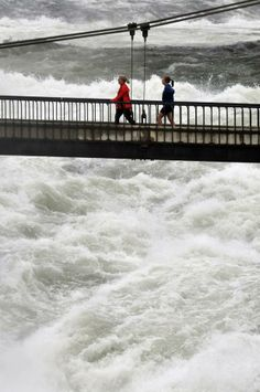 Rivers are rising: Joggers on a Riverfront Park foot bridge marvel at the thunderous sound and billowing mist of the Spokane River's middle falls in downtown Spokane on Thursday. Photo by Jesse Tinsley. #spokane #weather