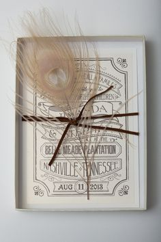 This rustic wedding invitation was mailed in an ivory box. The invitation was designed to look like a vintage rock concert poster. We tied a bleached peacock feather with a brown suede cording for a softer spin with a rock and roll edge. The response cards were designed as a ticket with a tear off stub for the accommodations. Click through to read more or Pin to save for later!
