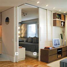 Ao invés de uma parede convencional, portas de correr garantem mais espaço ao ambiente e privacidade quando necessário.