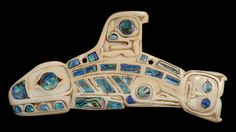 Carved bone ornament of a killer whale inlaid with haliotis shell. The ornament is flat and decorated on one side. The head of the whale is carved with formline design. The teeth and nose are inlaid with U-shaped pieces of haliotis shell, and the eye is inlaid with a round piece. In museum 1884. Canada. British Columbia Haida Gwaii (Queen Charlotte Islands) NW Coast.