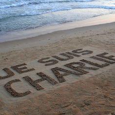 Un artista indiano realizza una scritta, sulla spiaggia di Puri, per le vittime della strage alla redazione di #CharlieHebdo avvenuta il 7 gennaio