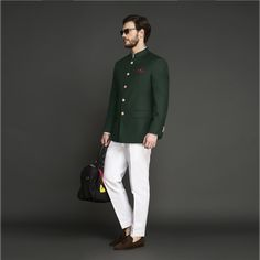 Emerald Green Jodhpuri Suit   This Emerald Green Jodhpuri Suit is a regal and sophisticated choice for a ceremonial wear. Crafted from Super 120s Italian wool fabric, the suit is darted and gives a neat silhouette and is paired with white pants made out of Italian milled long staple cotton fabric. The suit has luxurious hand painted buttons from Jaipur. This suit comes with a Jacket and a Trouser. #groomsmen #indianwedding #custom #jodhpuri Indian Men Fashion, Mens Fashion, Wool Fabric, Cotton Fabric, Wedding Suits, Wedding Attire, Sherwani, Groom Attire, Blazers For Men