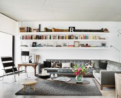 Long white bookshelves and gray couch/rug  From Aaron De Simone