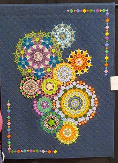 """""""My Summer in Venice"""" by Linda Cover. Linda was inspired by the millefiori glass she saw in Venice. She hand pieced the rosettes and used a pattern from Willyne Hammerstein."""