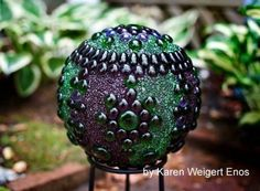 Garden art balls (spheres, globes) can be made from various repurposed items such as old bowling balls and glass lamp globes. This one is by artist Karen Weigert Enos.