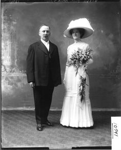 A dainty spriggy bouquet, with slender ribbons attaching a second hanging bouquet. Interesting idea!  John and Mrs. Delmore in wedding attire 1911