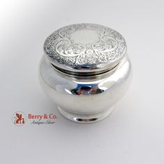 American sterling silver dresser jar with an engraved floral and scroll decoration with foliate accents on the lid by Wallace Silversmiths c.1900. The interior of the jar is gilt. The lid is marked 2. The base is marked 1. The base is also marked 837B11.