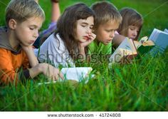 Kids are reading books on the green grass by kedrov, via ShutterStock