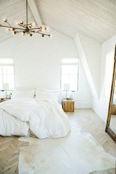 Simple bedroom with vaulted ceilings, painted white brick and white oak herringbone floors. Leanne Ford Interiors