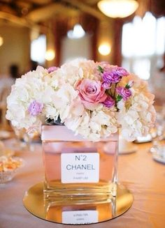 Here's fancy! White hydrangea, lilac pink mini rose, and purple spray carnations in a perfume bottle