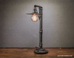 This industrial table lamp uses a 60 Watt Edison Bulb which hangs from a vintage style cloth cord and offers subtle but brilliant ambient