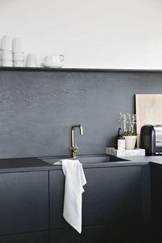 Sort køkken med sort bagvæg
