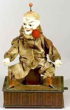 dolls, Germany, Lever-Operated Clown Juggler Automaton, Germany, circa 1880, with grimacing papier-mache [paper mache] face, upturned nose, black glass eyes, molded eyebrows, circus makeup and painted hair with a ball on spring at the center of his crown, sitting with outstretched arms on grained and checkered paper-covered base. A lever at the side causing the figure to turn his head and raise each arm alternately as a large red pom-pom revolves on a wire to simulate juggling, in the ...