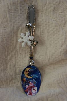 Snowman and crescent moon painting on a spoon, adorned with wire, snowflake ornament, and jingle bells for a winter feel.