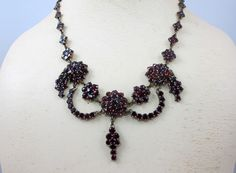 Stunning late 19th Century Bohemian Garnet Necklace with center Flower surrounded by smaller flower shaped links and attached garland dangle with another swaying dangle beneath it. Remainder of Neckla
