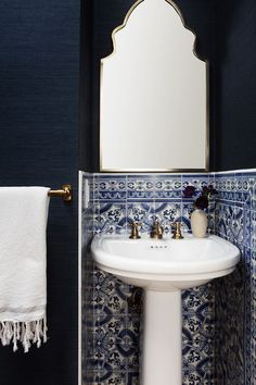 """Despite the small size of the powder room, Zwickl and Wollack wanted this space to have some major impact. So they paired a statement tile with a dark, textured wallpaper. """"We love when each bath..."""