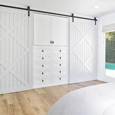 Bedroom Closet with Two Light Gray Barn Doors on Rails Flanking Built In Dresser
