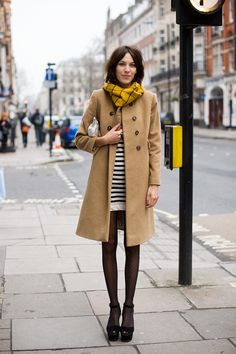 Yellow plaid infinity scarf, camel coat, striped dress, sheer black tights, and platform Mary Janes.