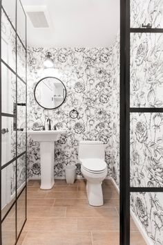 """Powder rooms may be small, but they present a great opportunity to experiment with bold designs to show off your style. """"I wanted to add something amusing and sophisticated. The large-scale pattern, absent of color, makes the small bathroom pop without looking too busy"""", this renovator shared. Explore all three bathrooms—packed with personality—in this Brooklyn loft reno. Custom Cabinet Doors, Bathroom Wallpaper, Bold Wallpaper, Wallpaper Ideas, Double Sink Vanity, Black And White Wallpaper, Small Bathroom, Bathrooms, Bathroom Kids"""