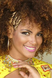 "Clara Paixão is from the Carnaval bloco Cacique de Ramos & the Beija-Flor Samba School of Nilópolis, Rio de Janeiro. After wearing waist length weaves in past ""Queen of Carnaval"" competitions, she decided to transition into wearing her natural, curly hair texture."