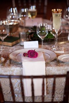White and gold chargers with gold flat ware are perfect matches with this gold/ivory lace linen. The fuchsia flower on top of the menu is perfect for this rustic indoor California Wine Country wedding.