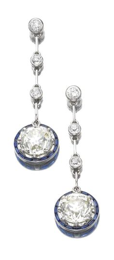 A pair of Art Deco sapphire and diamond pendent earrings, circa 1920. Each circular-cut diamond within a calibré-cut sapphire border, to a line of three collet-set circular-cut diamonds, screw back fittings.