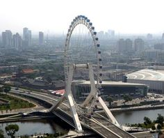 Tianjin, China. 394 foot tall Ferris wheel in centre of a bridge as diversion for commuters stuck in traffic.  48 capsules, room for 8 in each, rotation is 1/2 hr.