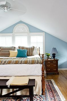 This master bedroom has a steep roofline. A Palladian window with a fan detail keeps the room bright. Paint: @benjamin_moore Aura zero-VOC in AF-535 Serenata