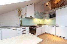 Kuchyň je velkorysá co do úložných prostor, tak i do pracovní plochy. Na zadní stěně linky je namísto obkladu použito kalené sklo, které působí efektně; Archiv firmy