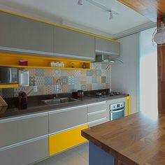 """A cozinha é marcada pelo amarelo e o porcelanato com estilo patchwork. Para os moradores foi uma ótima solução já que o porcelanato tem fácil manutenção e limpeza. """"Adoramos a nossa cozinha. Ela é um espaço de criatividade onde podemos relaxar, inventar e misturar receitas. A bancada grande e os utensílios que escolhemos nos ajudam bastante. Costumamos cozinhar juntos e sempre saem coisas muito boas. Pensamos em cada detalhe e não tenho dúvidas que temos a morada dos nossos sonhos""""."""