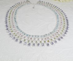 This statement necklace is woven in a collar style with silver lined glass seed beads and Czech glass beads in lovely metallic spring colors of pink, lavender, blue and green. The total width is just over 1 and length 18 with a 1.5 extender chain finished with a drop. Spring ring clasp. Surprisingly lightweight and easy to wear.   https://www.etsy.com/shop/IndulgedGirl