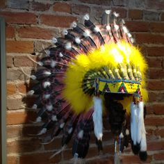 This Yellow Halo Headdress was worn as a form of status revealing ranks among warriors among the Sioux, Crow, Cheyenne, Blackfeet, Assinniboine and Plains Cree. Each feather was earned by counting coup, brave deeds or other accomplishments This carefully crafted art piece includes hand-painted white turkey feathers to imitate eagle feathers. The red feathers symbolize strength, vitality/life force, good fortune and good health. The custom lazy bead work on the brow band and detailed accents…