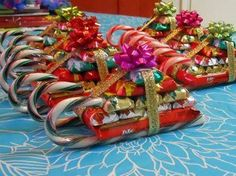 Holiday treat sleighs:  hot glue gun, two candy canes, Kit Kat bar, other candy bars smaller than the Kit Kat, and ribbon.  Hot glue the Kit Kat to the candy canes, stack the rest of the treats and tie with a ribbon.  Super easy and cute!
